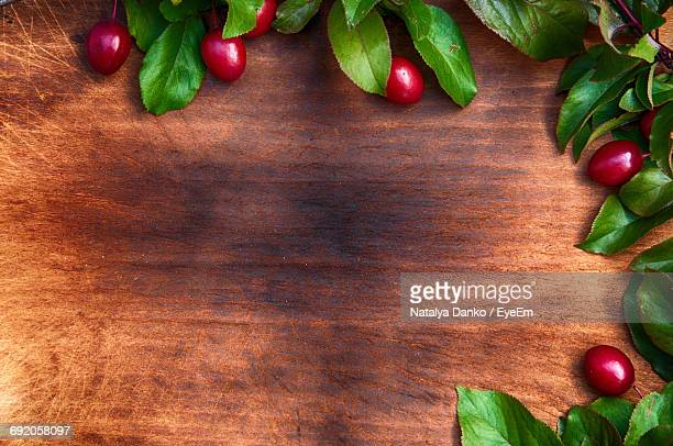Directly Above Shot Of Red Berries Arranged On Border Of Wooden Table