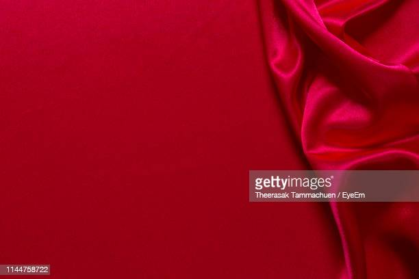 directly above shot of red crumpled satin on bed - silk stock pictures, royalty-free photos & images