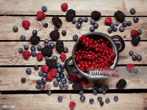 directly above shot of red currants in container surrounded with berry fruits on table - berry fruit stock pictures, royalty-free photos & images