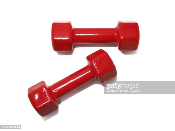 directly above shot of red dumbbells on white background - dumbbell stock pictures, royalty-free photos & images