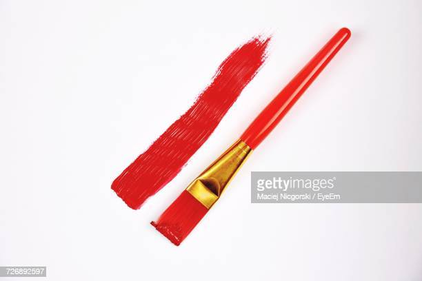 Directly Above Shot Of Red Paint With Brush On White Background