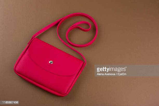 directly above shot of red purse on brown table - sac à main rouge photos et images de collection