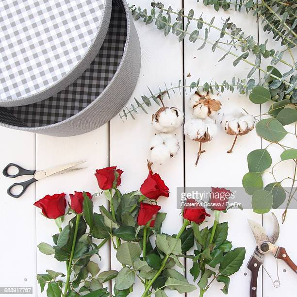 Directly Above Shot Of Red Roses And Scissors On Table