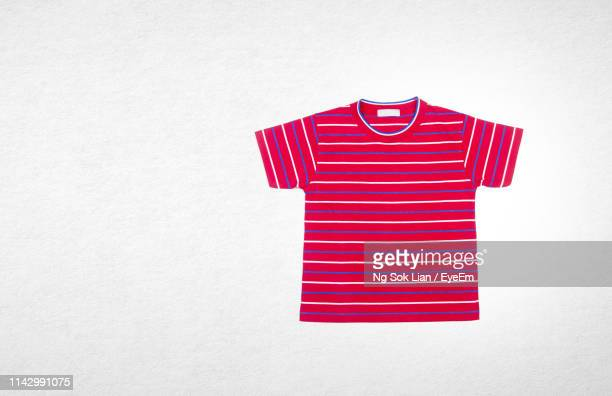 directly above shot of red t-shirt against white background - ボーダーシャツ ストックフォトと画像