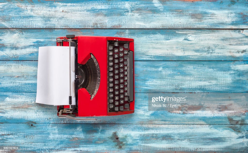Directly Above Shot Of Red Typewriter With Blank Paper On Table : Stock Photo