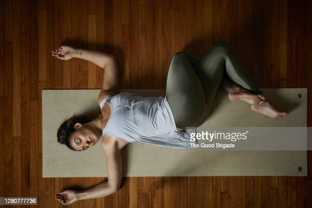 directly above shot of relaxed young woman doing yoga on exercise mat in studio - lying down 個照片及圖片檔