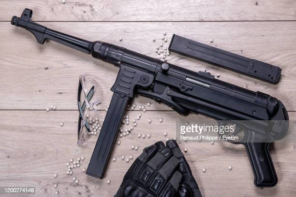 directly above shot of rifle and protective eyewear and glove on textile - machine gun stock pictures, royalty-free photos & images