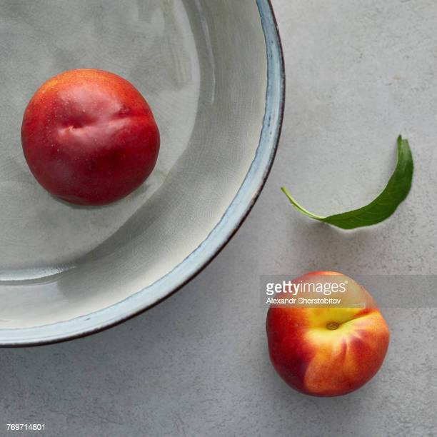 Directly above shot of ripe peaches on table an container