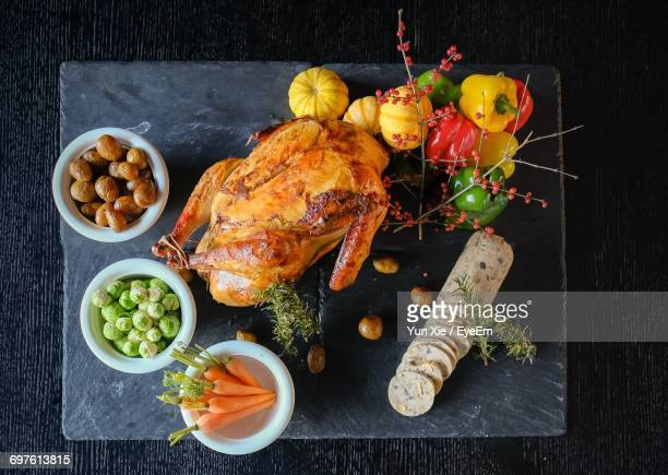 Directly Above Shot Of Roasted Chicken By Bell Peppers On Slate At Table
