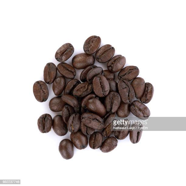 directly above shot of roasted coffee beans against white background - coffee beans stock photos and pictures