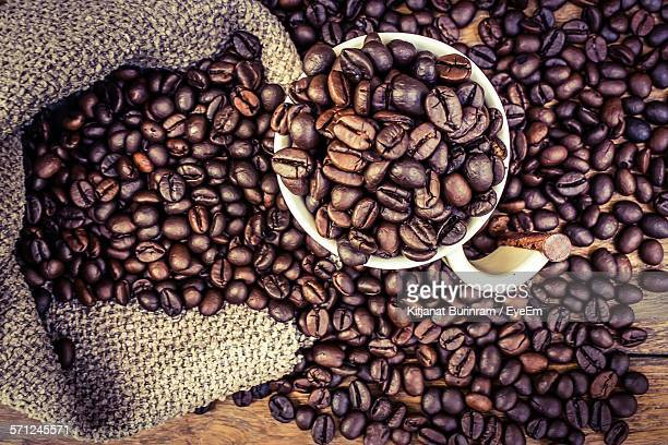 Directly Above Shot Of Roasted Coffee Beans In Cup And On Table