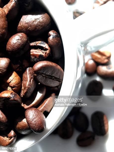 directly above shot of roasted coffee beans in cup on table - nathalie pellenkoft stock pictures, royalty-free photos & images