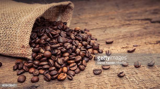 directly above shot of roasted coffee beans on table - roasted coffee bean stock photos and pictures