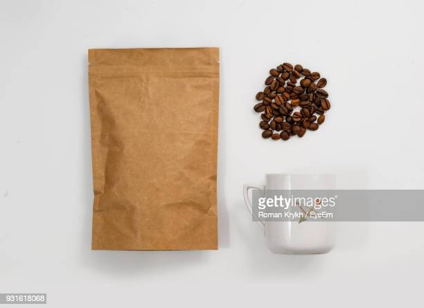 directly above shot of roasted coffee beans with cup and paper bag on white background - bag stock photos and pictures