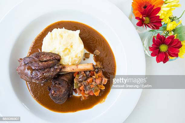 Directly Above Shot Of Roasted Lamp Shank With Mashed Potatoes On Table