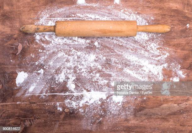 directly above shot of rolling pin with flour on wooden table - mehl stock-fotos und bilder