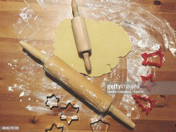 Directly Above Shot Of Rolling Pins On Cookie Dough By Pastry Cutter