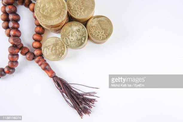directly above shot of rosary beads with stacked coins on gray background - islam stock pictures, royalty-free photos & images