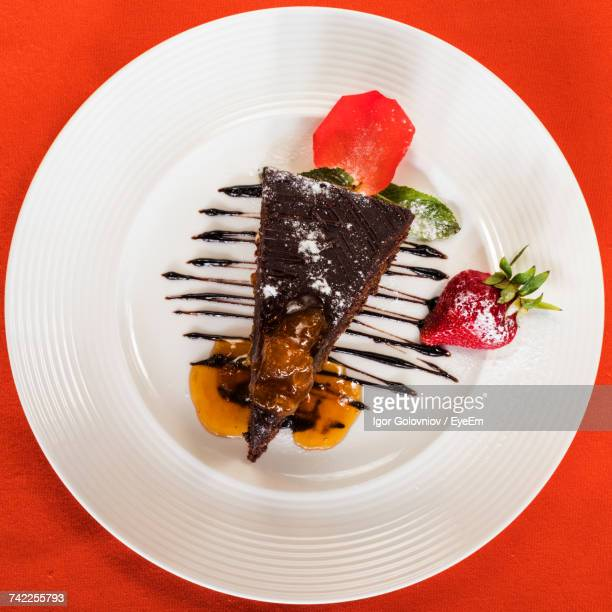 Directly Above Shot Of Sacher Cake Served With Strawberry In Plate On Red Table