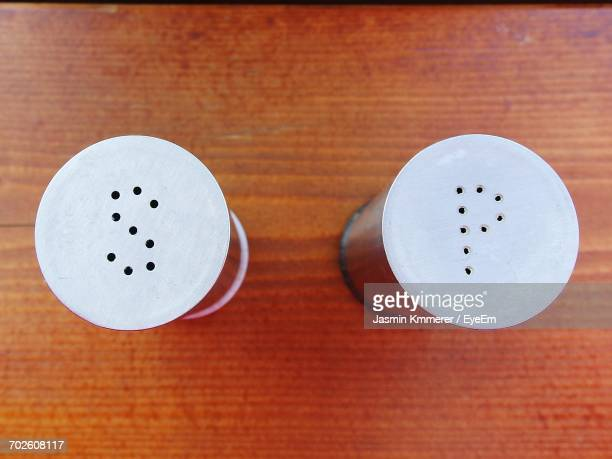 Directly Above Shot Of Salt And Pepper Shakers On Wooden Table