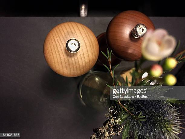 Directly Above Shot Of Salt And Pepper Shakers With Vase On Table At Restaurant