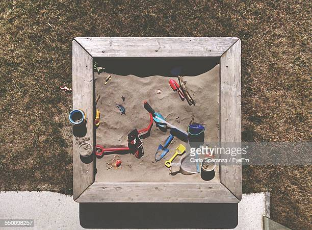 Directly Above Shot Of Sandbox With Toys At Backyard