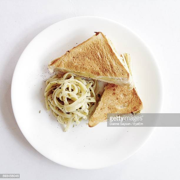 Directly Above Shot Of Sandwich And Pasta In Plate Against White Background