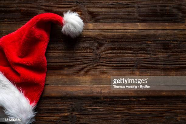 directly above shot of santa hat on wooden table - brown thomas christmas stock pictures, royalty-free photos & images