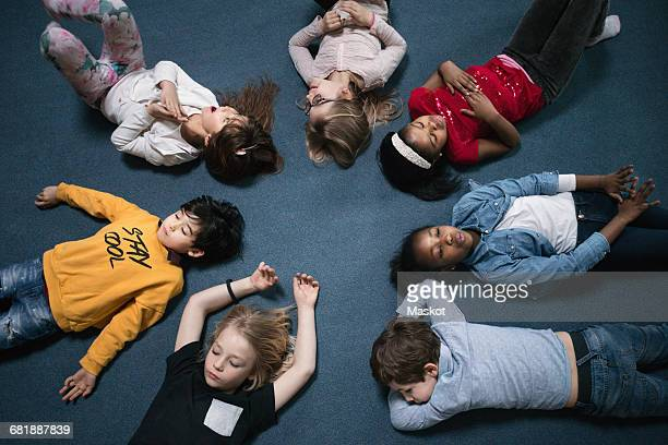 Directly above shot of school children lying on floor in classroom