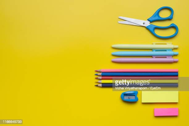 directly above shot of school supplies on yellow background - school supplies stock pictures, royalty-free photos & images