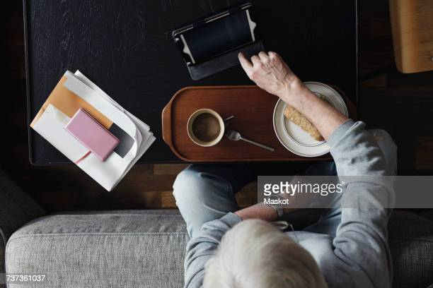 directly above shot of senior man using digital tablet while having breakfast at home - one senior man only stock pictures, royalty-free photos & images