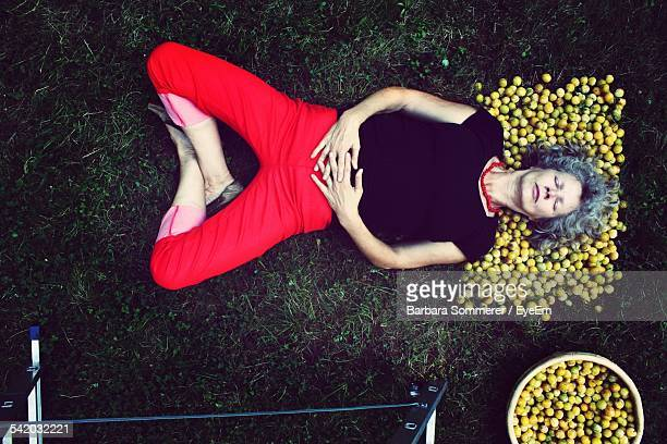Directly Above Shot Of Senior Woman Lying On Lemons At Field