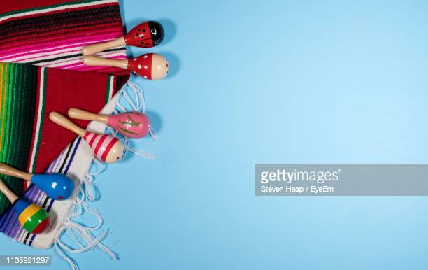 directly above shot of serape and maracas on blue background - maraca stock photos and pictures