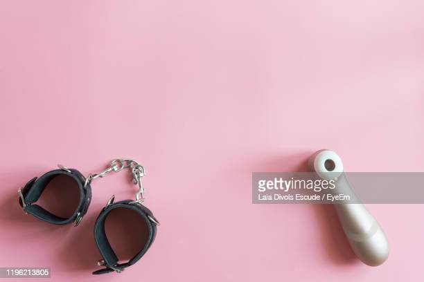 directly above shot of sex toy and fetish wear on pink background - consolador fotografías e imágenes de stock