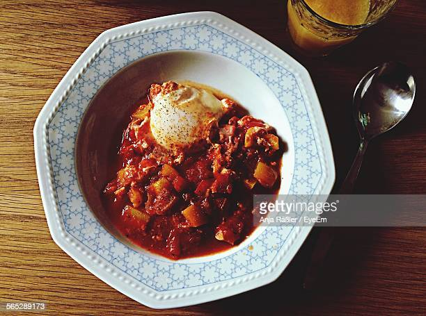 directly above shot of shakshouka in plate on table - anja bayer stock-fotos und bilder