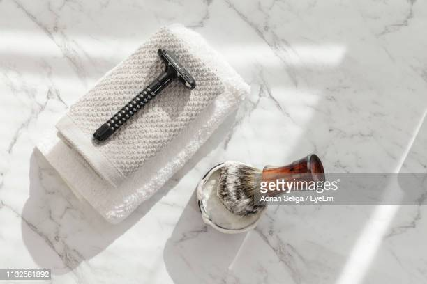 directly above shot of shaving brush and razor on marble floor - shaving brush stock photos and pictures