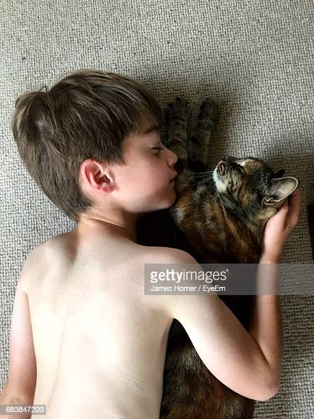 Directly Above Shot Of Shirtless Boy With Cat Sleeping On Carpet