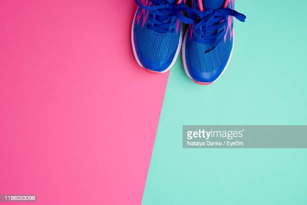 directly above shot of shoes against colored background - sports footwear stock pictures, royalty-free photos & images