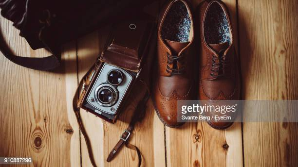directly above shot of shoes and camera on floorboard - brown shoe stock pictures, royalty-free photos & images