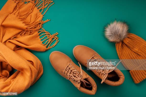 directly above shot of shoes and knit hat by scarf on table - brown shoe stock photos and pictures