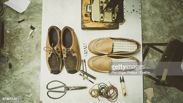 Directly Above Shot Of Shoes And Work Tools In Cobbler Workshop