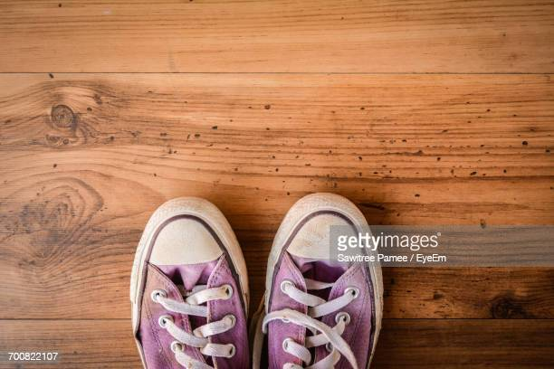 Directly Above Shot Of Shoes On Wooden Floor