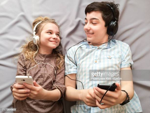 Directly Above Shot Of Siblings Using Smart Phone While Lying On Bed At Home