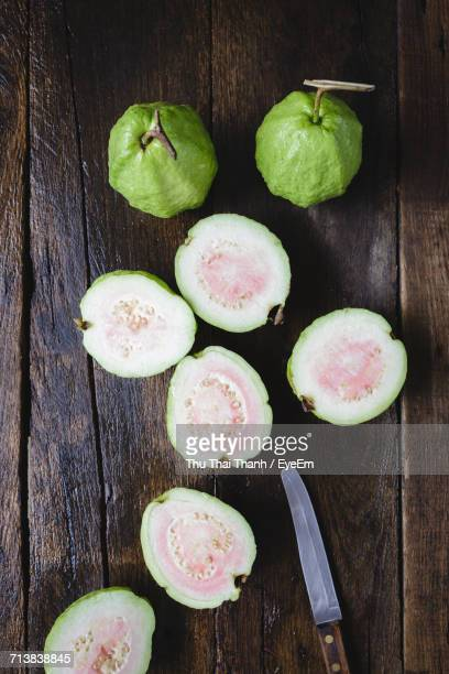 directly above shot of sliced guavas with table knife on wooden table - guava fruit stock photos and pictures