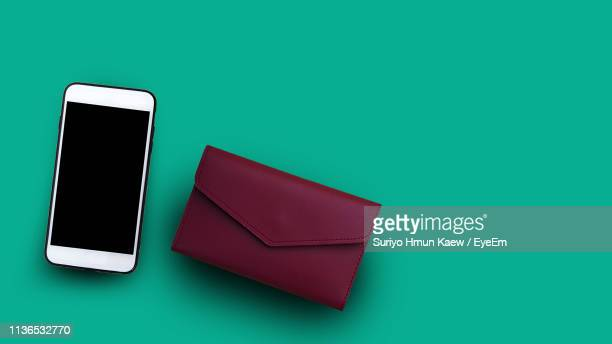 directly above shot of smart phone clutch bag on turquoise background - pochette borsetta foto e immagini stock