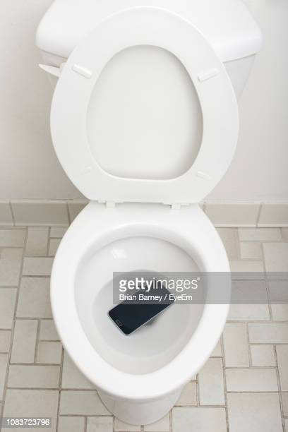 directly above shot of smart phone in toilet bowl at bathroom - toilet bowl stock photos and pictures