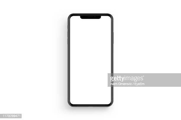 directly above shot of smart phone with blank screen against white background - white background stockfoto's en -beelden