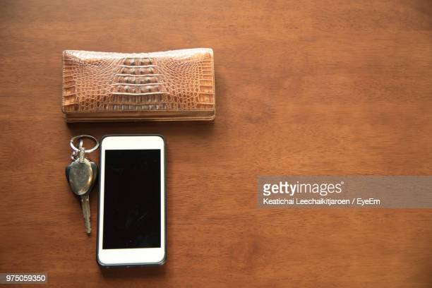 directly above shot of smart phone with purse and car key on table - 机 木 ストックフォトと画像