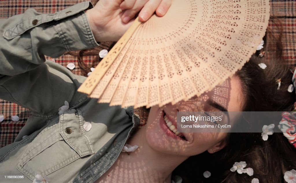 Directly Above Shot Of Smiling Girl Holding Hand Fan While Lying On Textile : Stockfoto