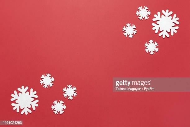 directly above shot of snowflakes against red background - snowflake stock pictures, royalty-free photos & images
